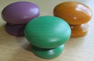 Bright coloured wooden cupboard knobs in lilac, apple green and yellow